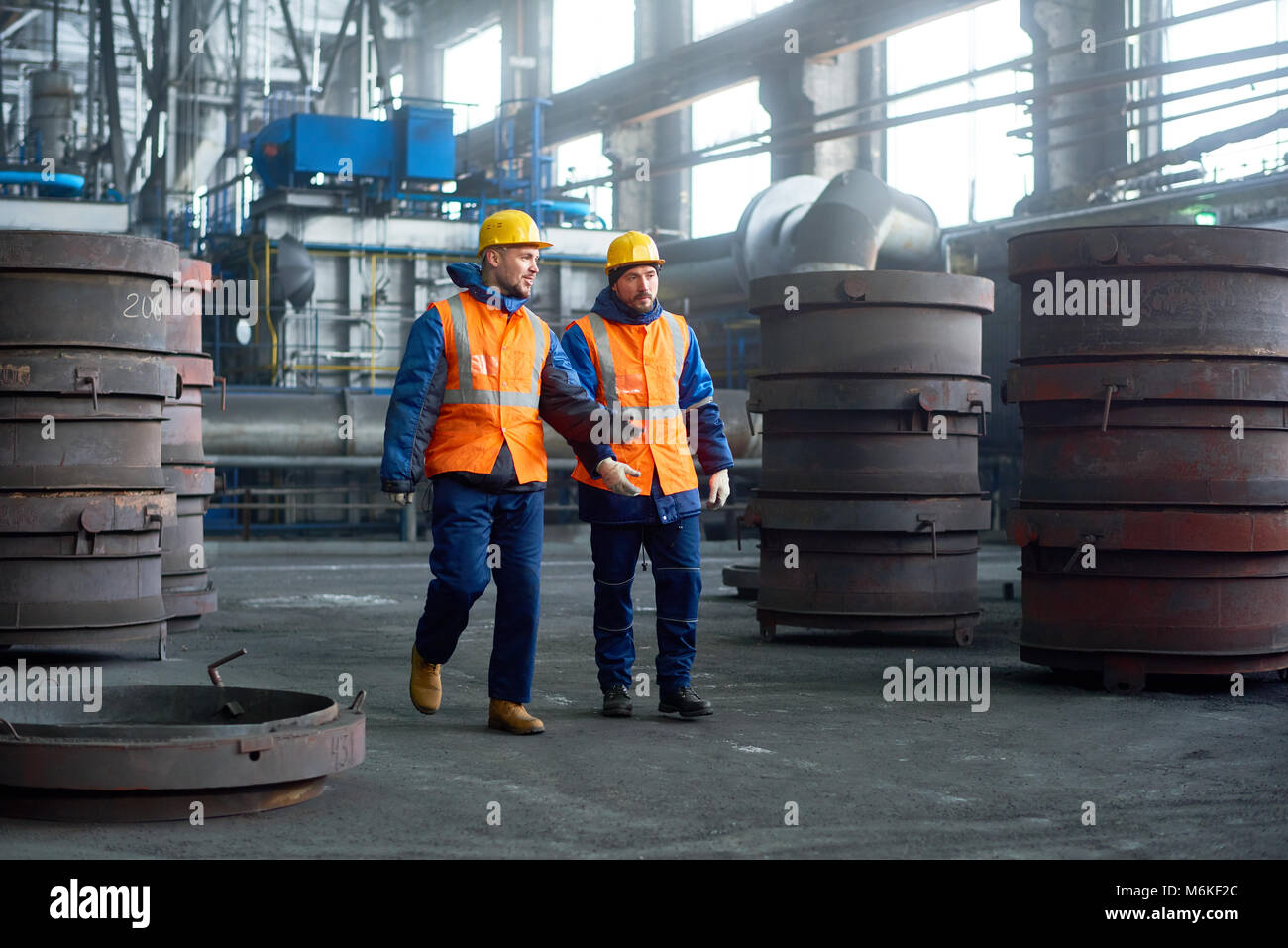 Two Technicians Walking Along Production Department Stock Photo