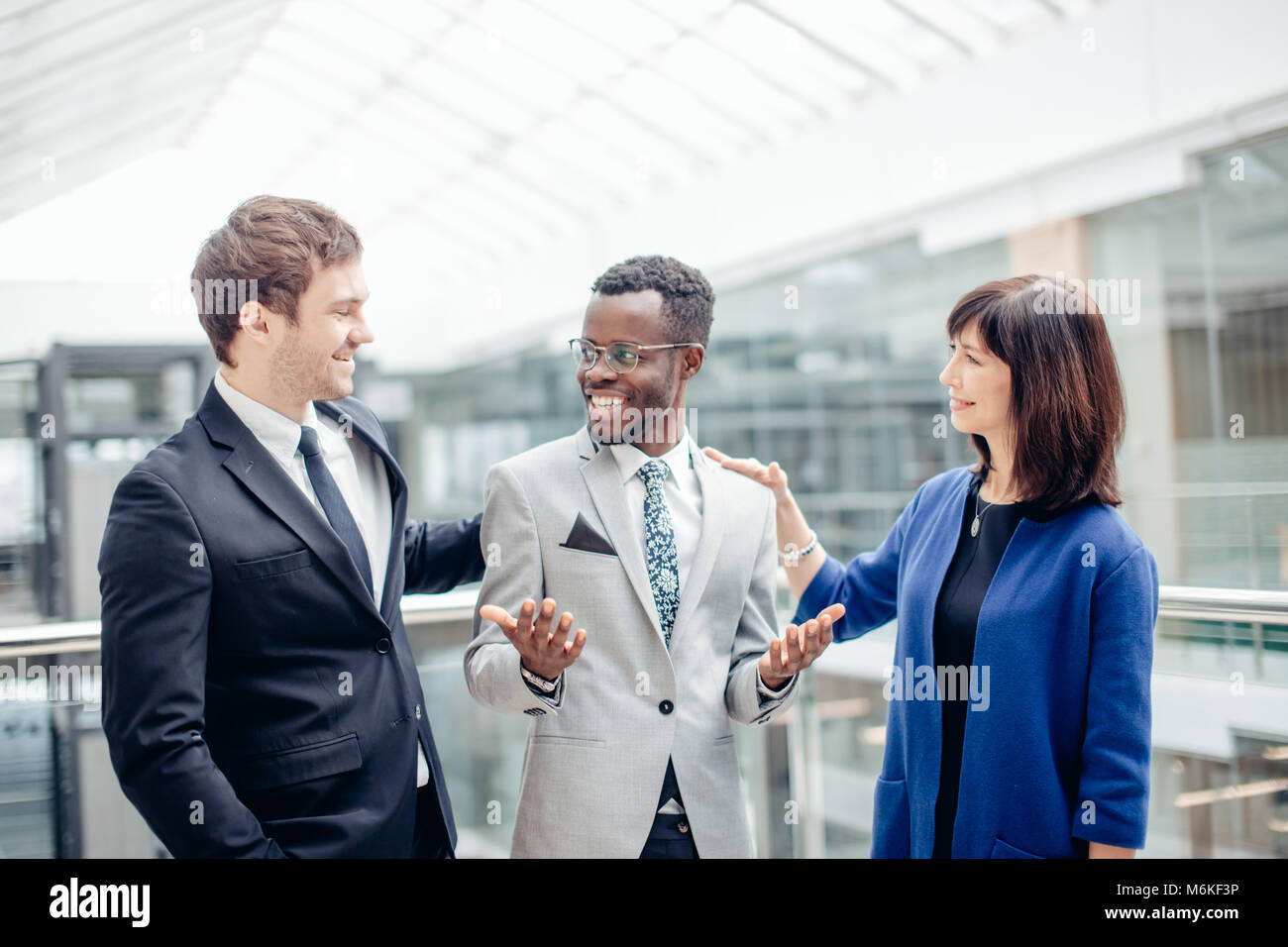 Multiracial Business Team congratulate For Success Of afroamerican Colleague - Stock Image