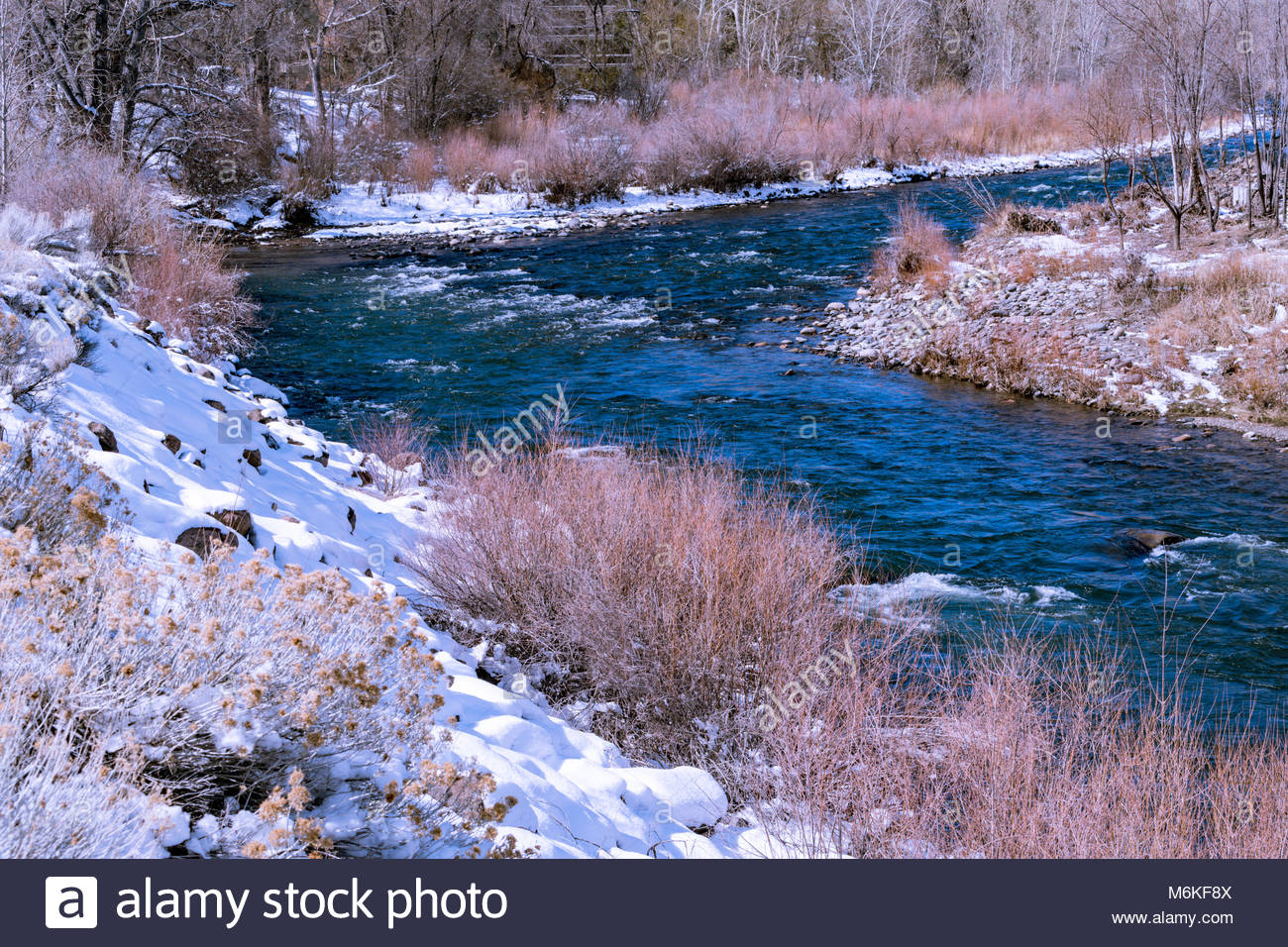 Snowy banks along the Truckee River in Northern Nevada near Idlewild park. - Stock Image