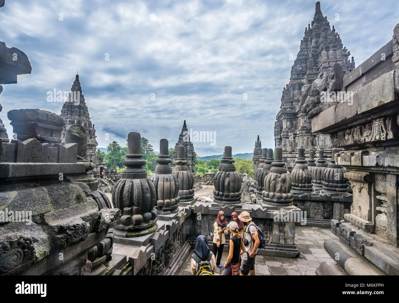 Indonesia, Central Java, visitors explore the bas-relief galleries along the balustrades of the Shiva temple at - Stock Image