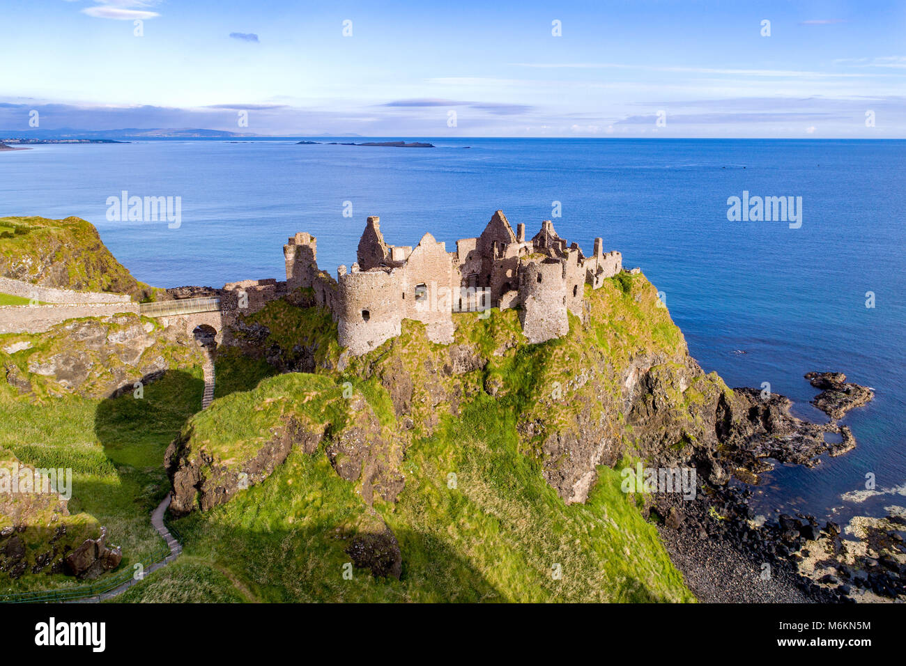 Ruins of medieval Dunluce Castle on a steep cliff. Northern coast of County Antrim, Northern Ireland, UK. Aerial - Stock Image