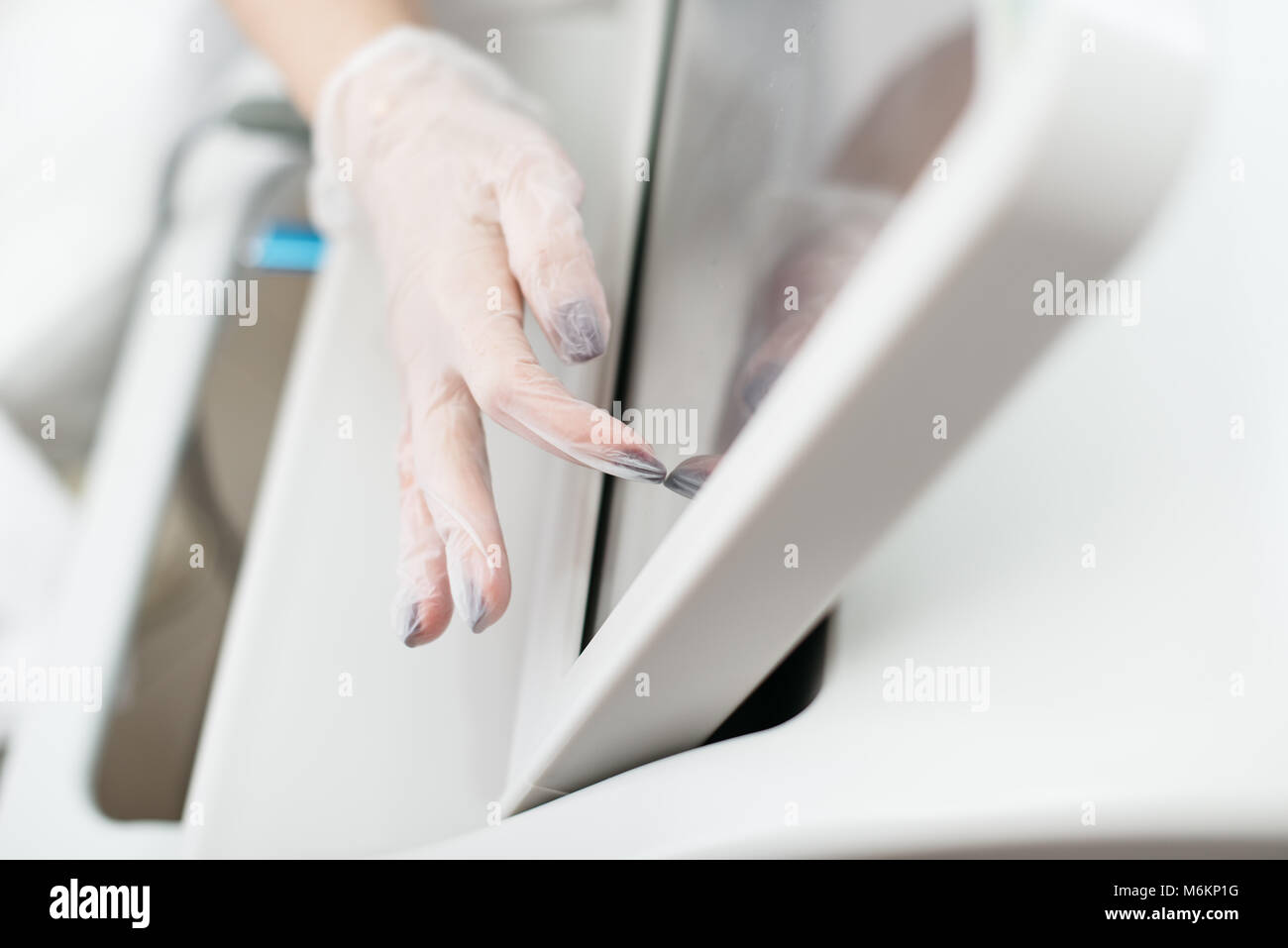 Female hands in polyethylene gloves touching the screen of laser apparatus to turn it on. No face. Close-up. - Stock Image