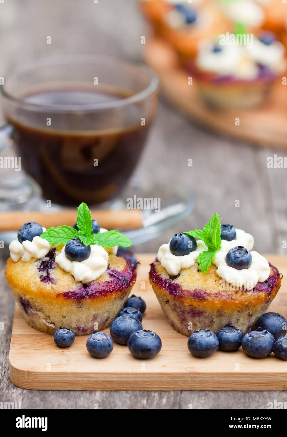 fresh  muffins with blueberry and cup of coffee on wooden background Stock Photo