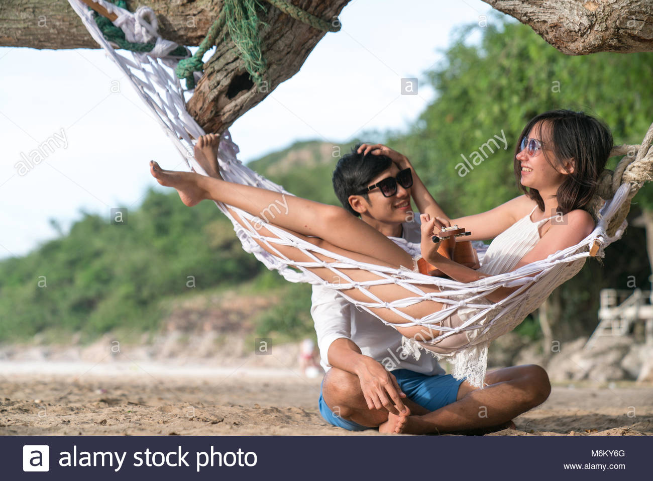 couple lover enjoy honeymoon and long vacation on the sea beach, siiting on the swing together relax and confortable, Stock Photo