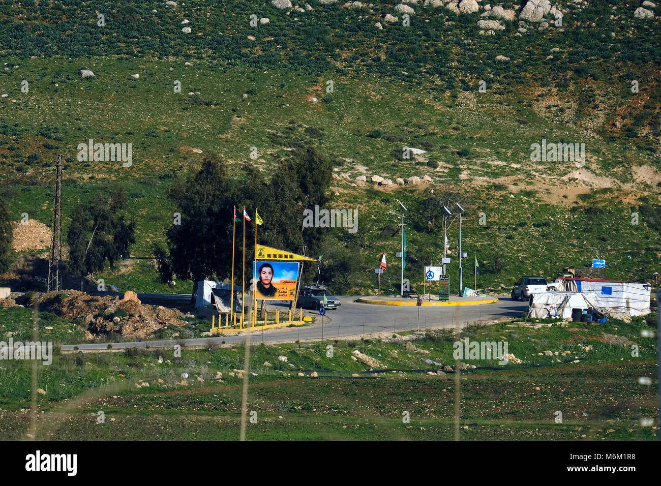 Cars driving past the Palestinian, Lebanese and Hezbollah movement flags in the southern Lebanese village of Kfar - Stock Image