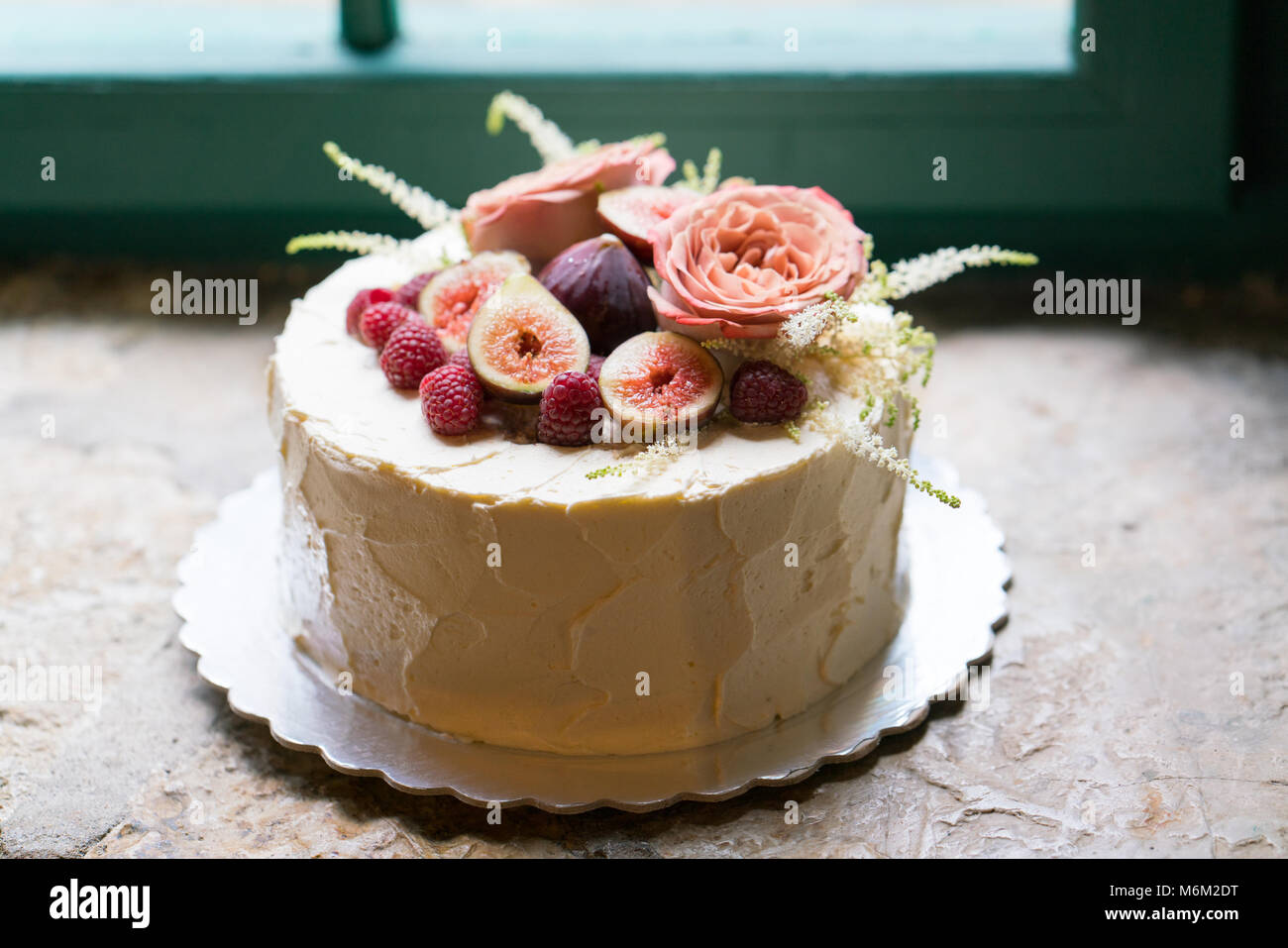 Homemade wedding cake decorated with flowers and fruits - Stock Image