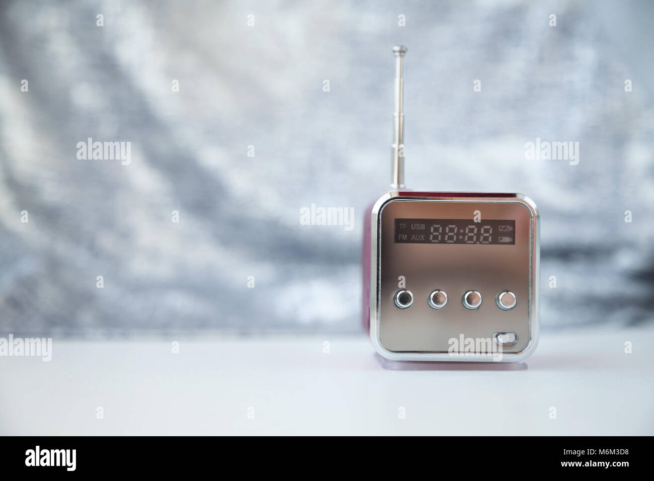 Cute little modern radio with antenna on a gray background. New reflecting cube radio receiver with copy space. - Stock Image