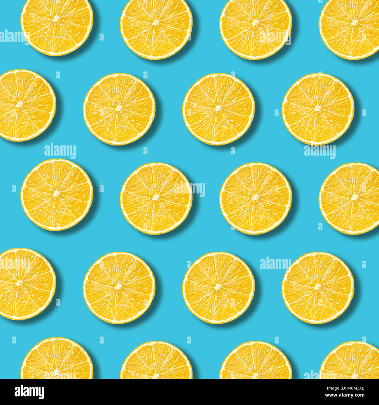 Lemon slices pattern on vibrant turquoise color background. Minimal flat lay food texture - Stock Image