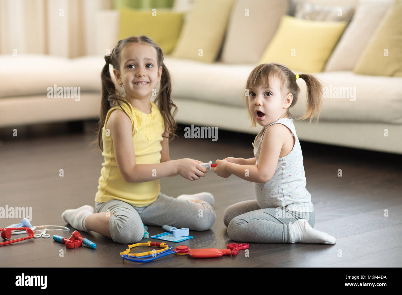 Conflict between little sisters playing at home. Kids are fighting, toddler girl takes toy, sibling relationships - Stock Image