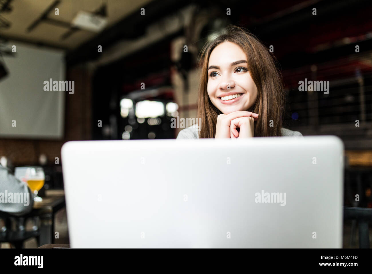 beautiful happy woman working on laptop computer during coffee break in cafe bar - Stock Image