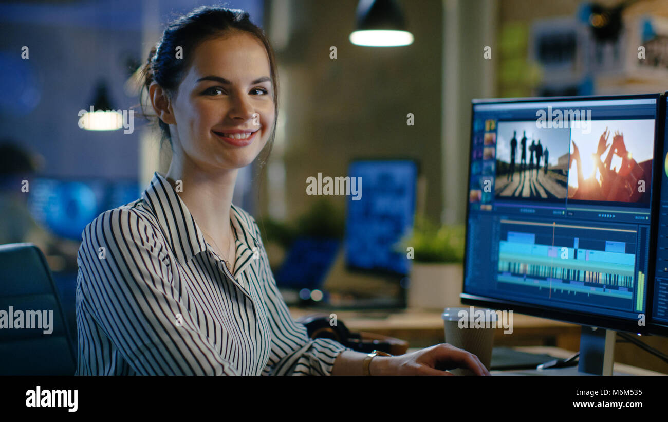 Female Video Editor Turns and Warmly Smiles into the Camera. Her Office is Modern and Creative Loft Studio. - Stock Image