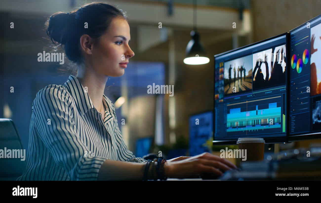 Female Video Editor Works with Footage and Sound on Her Personal Computer. She Works Late. Her Office is Modern - Stock Image