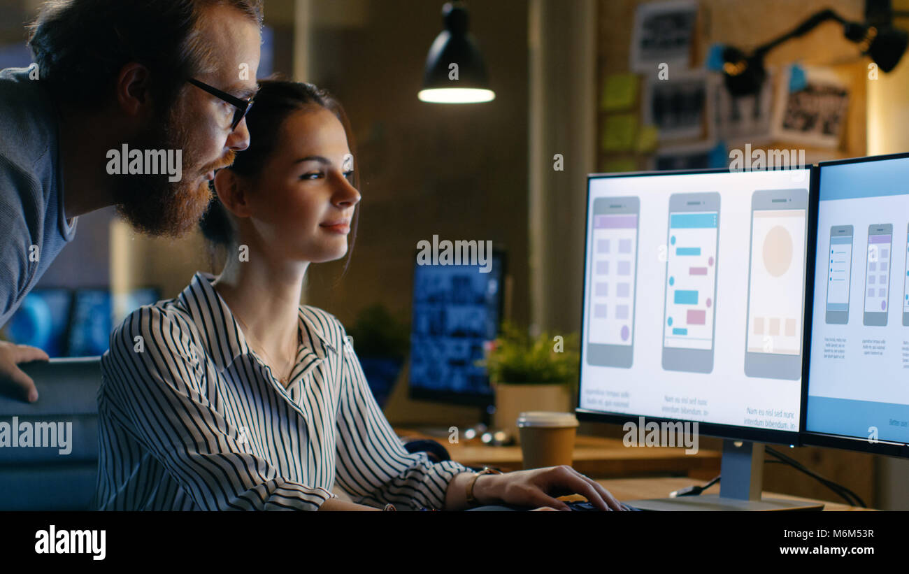 Female UX Architect Has Discussion with Male Design Engineer, They Work on Mobile Application Late at Night, She - Stock Image