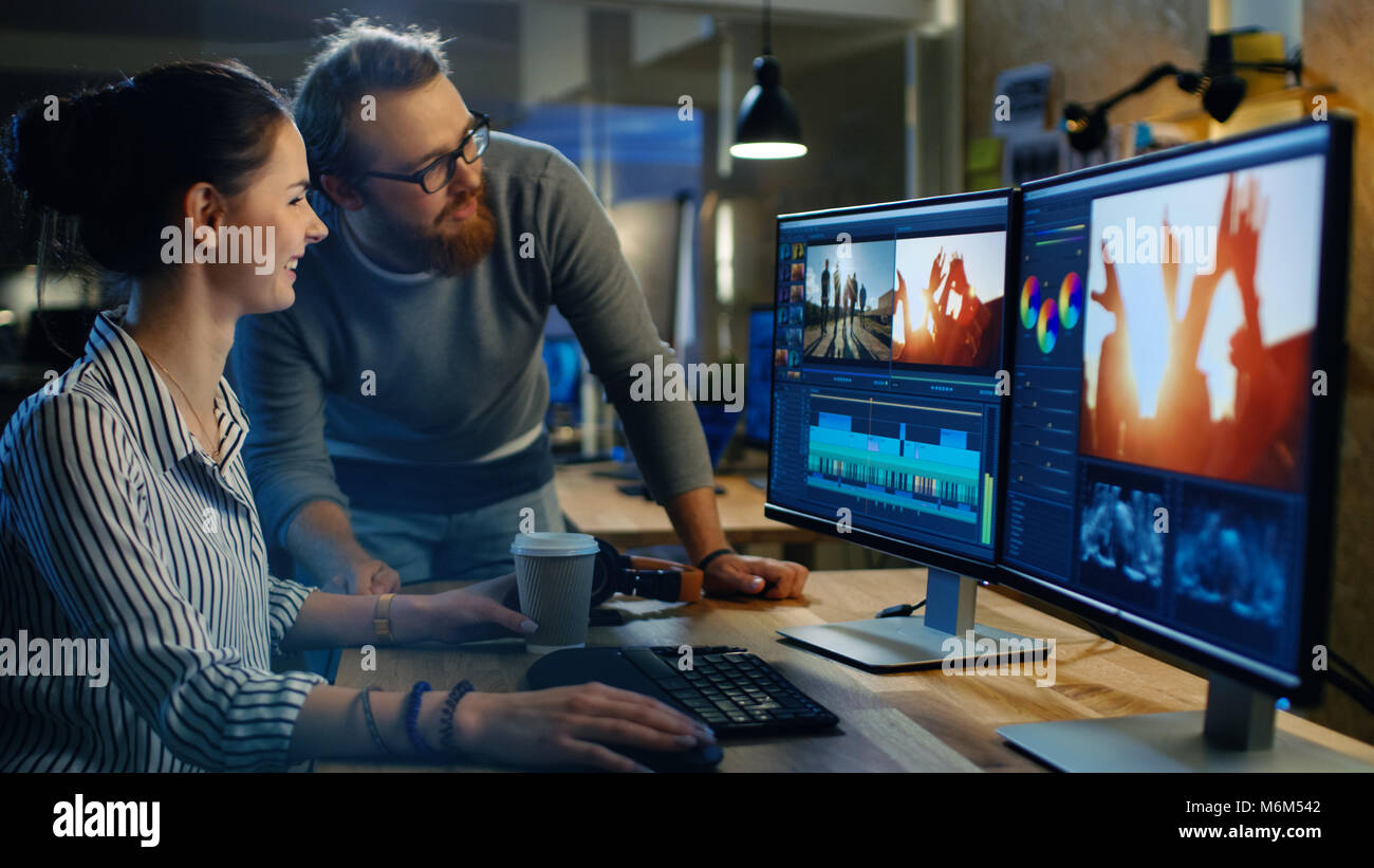 Female Video and Sound Editor Works With Her Male Colleague on Project on Her Personal Computer with Two Displays. - Stock Image