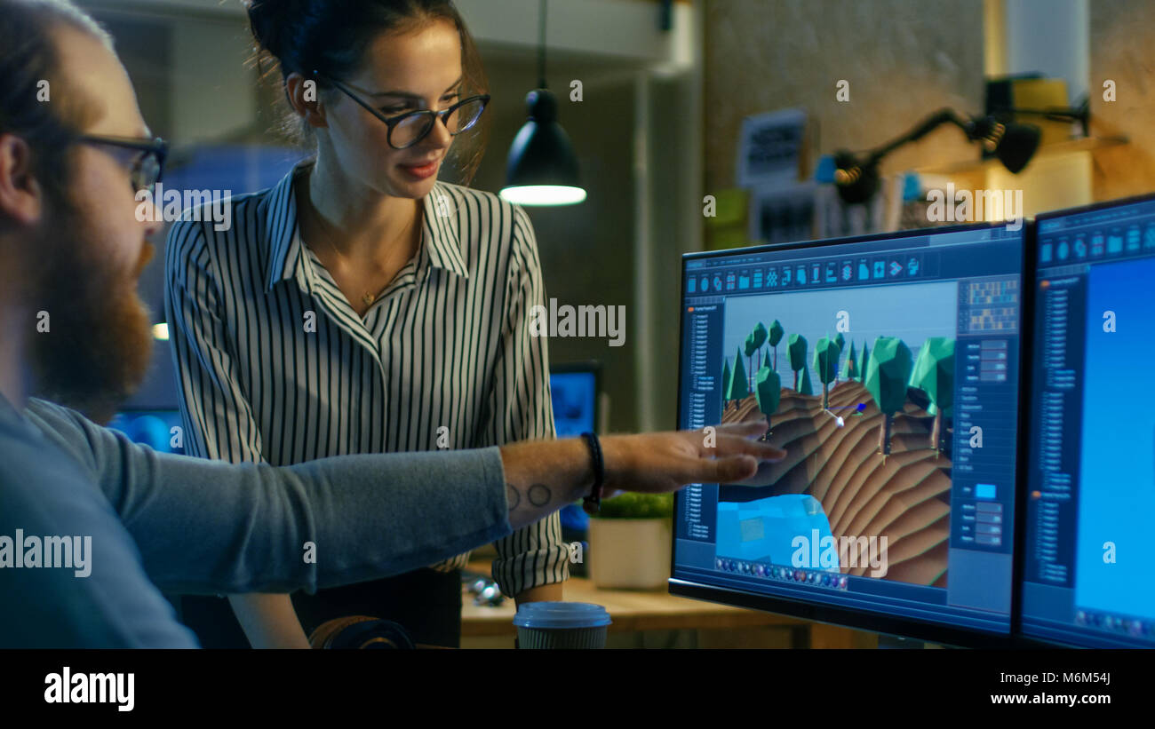 Male Game Developer Talks with Artistic Female Level Designer. Two Displays Show Totally Original Game. They Work - Stock Image