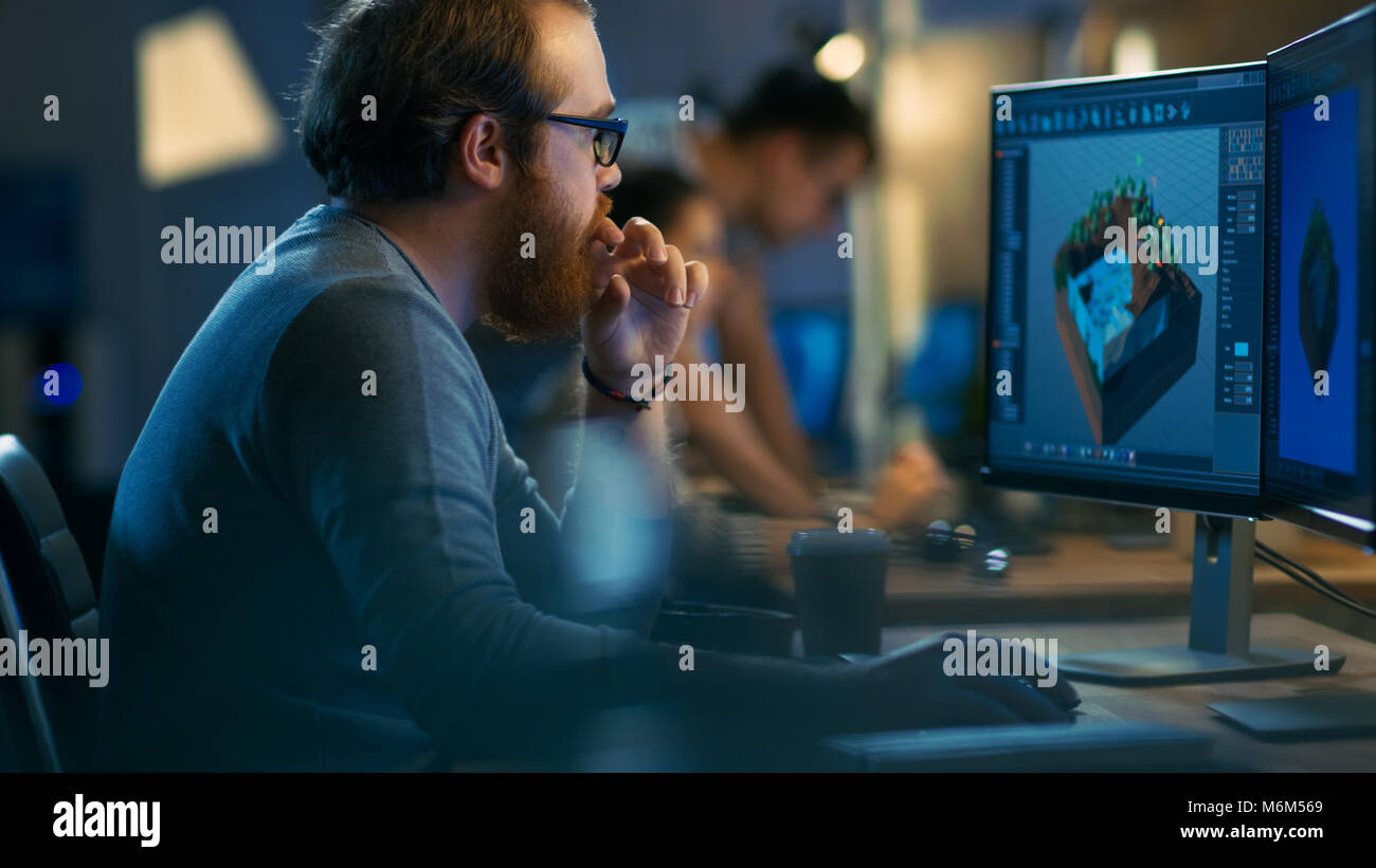 Male Game Developer works on a Level Design on His Personal Computer with Two Displays. He Works for in a Creative - Stock Image
