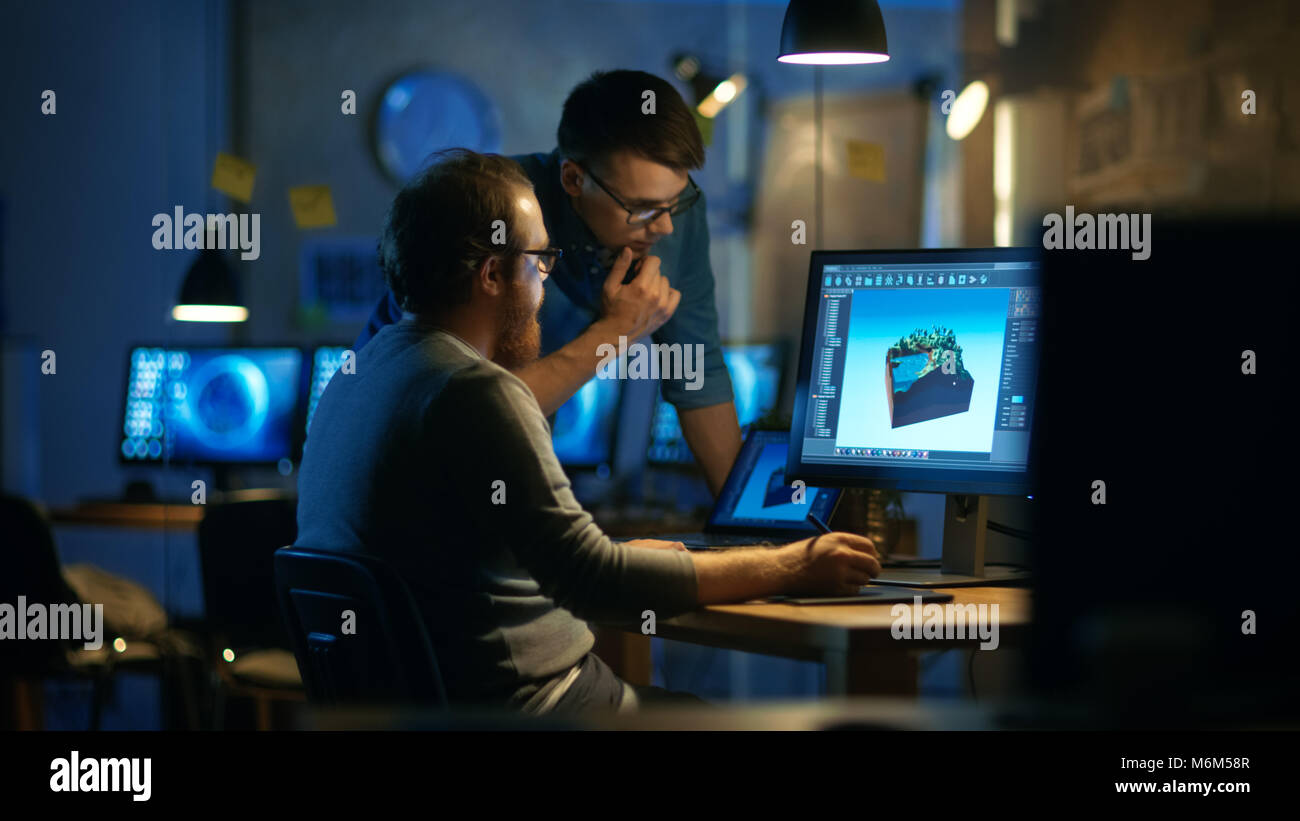 Two Male Game Developers Discuss Game Level Drawing, One Uses Graphic Tablet. They Work Late at Night in a Loft - Stock Image