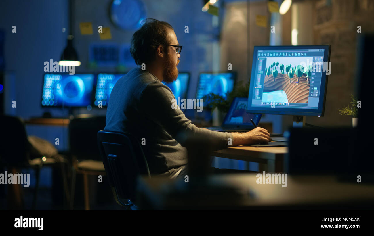 Male Mobile Application Developer Works with Graphics on His Personal Computer with Two Monitors. He Works Late - Stock Image