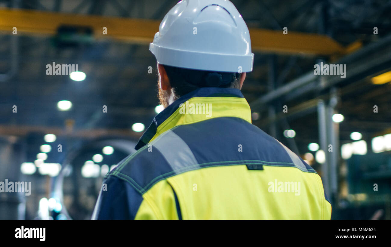 Industrial Engineer in Hard Hat and Safety Jacket Looks Around in Big Heavy Industry Manufacturing Factory. - Stock Image