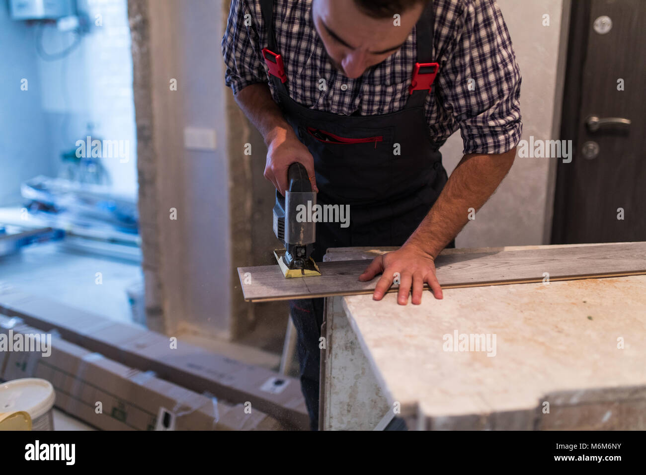 Contractor Cutting laminate flooring lengthwise. Workers Cutting laminate flooring with electric saw. - Stock Image
