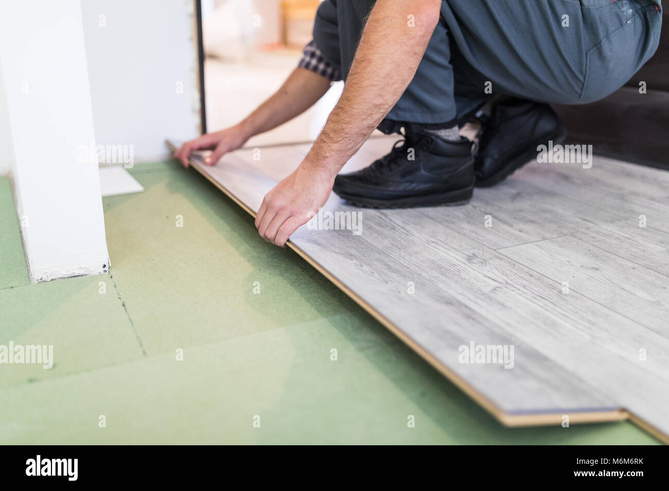 Close up man hands worker installing laminate flooring in the new room - Stock Image