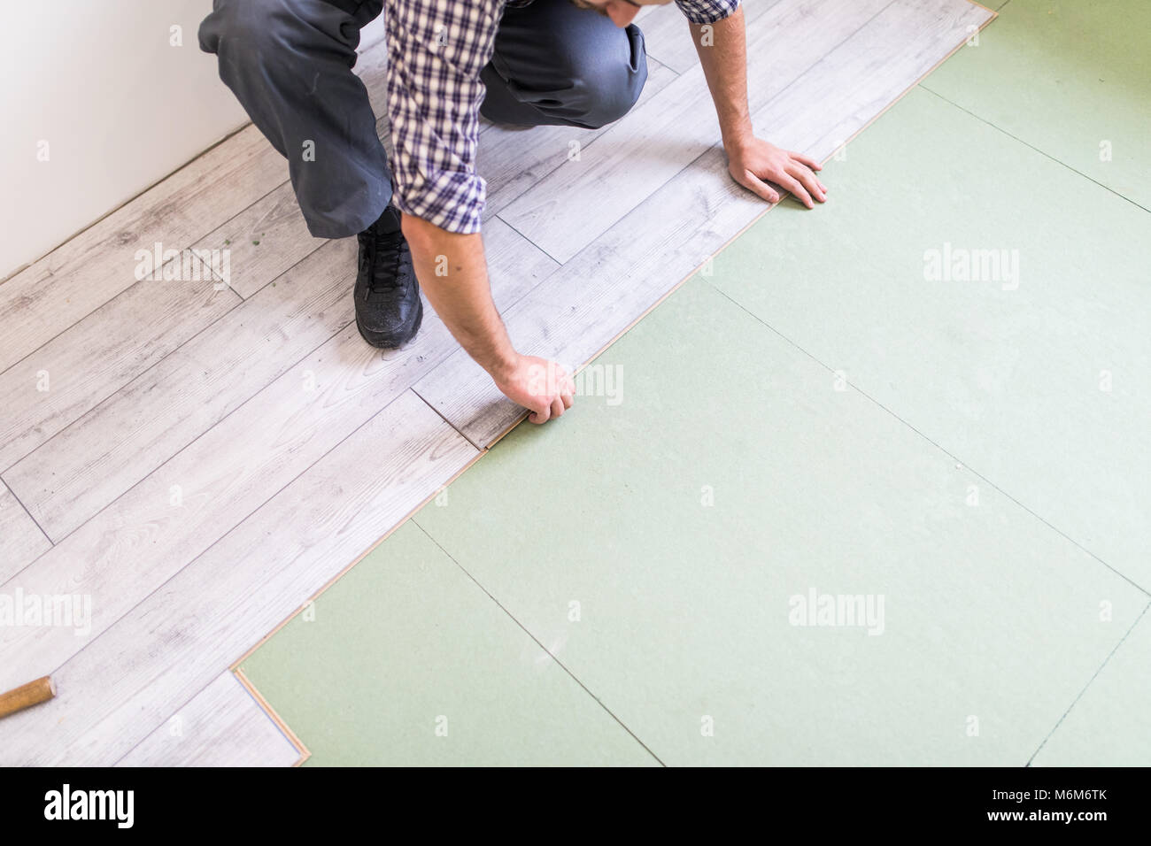 carpenter worker installing laminate flooring in the room - Stock Image