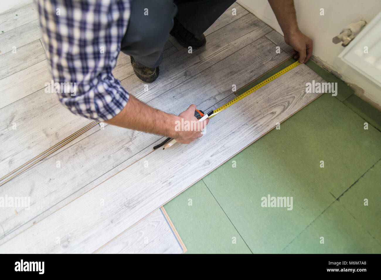 Close-up Of A Worker Drawing A Mark On Laminate Using Ruler - Stock Image
