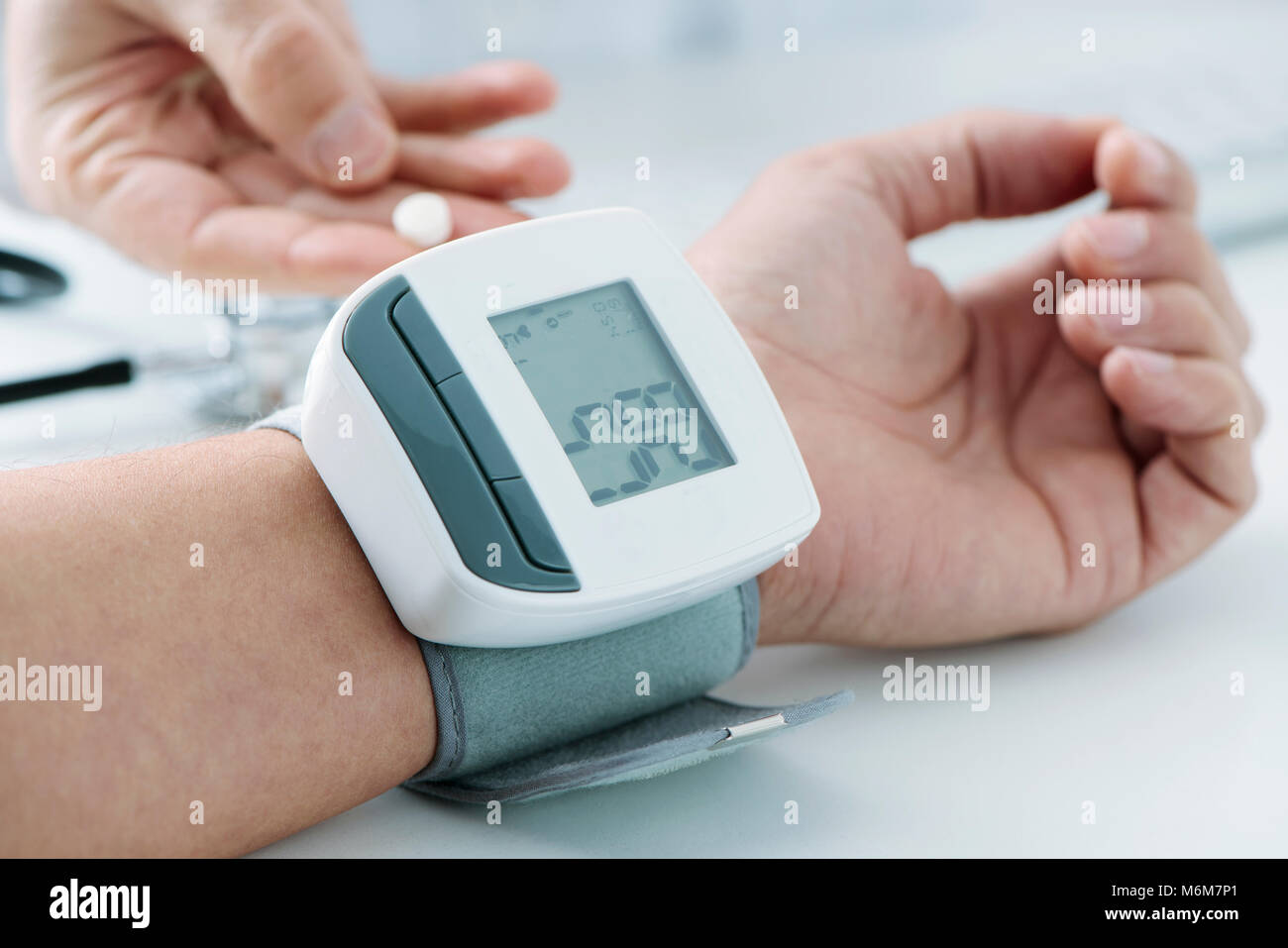 closeup of a young a caucasian patient man at the doctors office whose blood pressure is being measured with a sphygmomanometer, - Stock Image