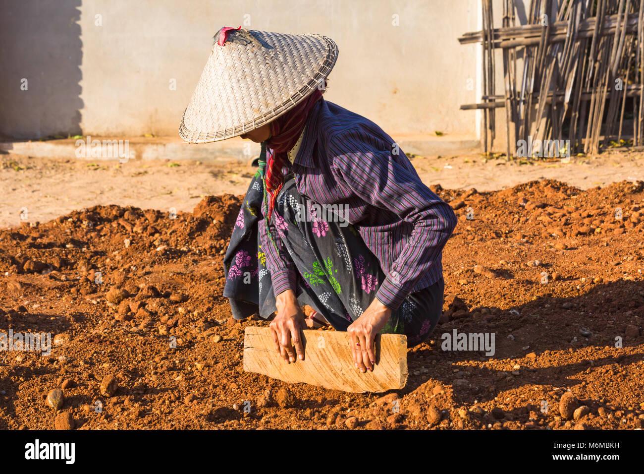 Villagers undertake manual road construction work at West Phwar Saw Village, Bagan, Myanmar (Burma), Asia - woman - Stock Image