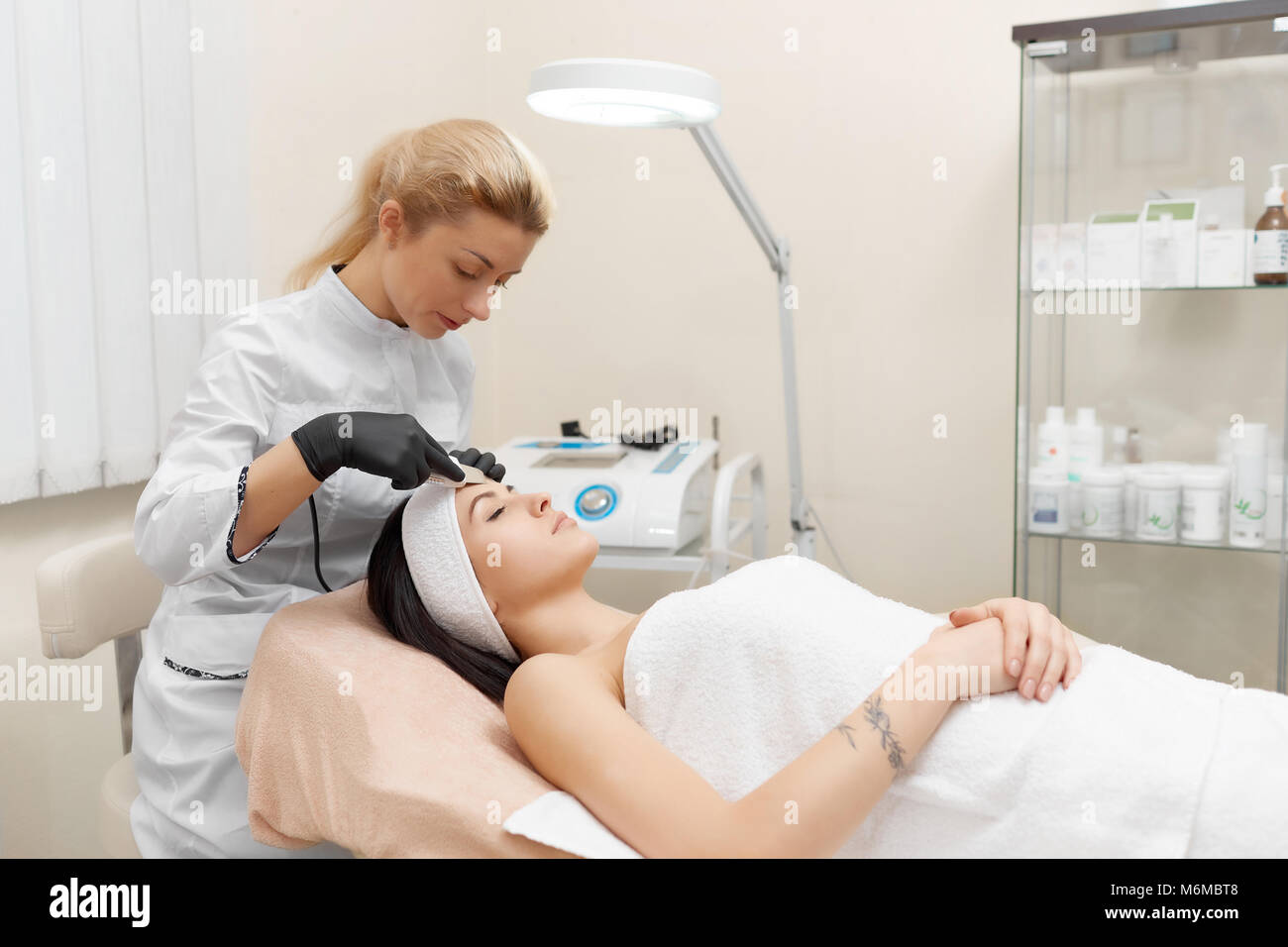 Hardware cosmetology. Cosmetologist doing procedure of ultrasonic cleaning of face. Young woman getting ultrasonic - Stock Image