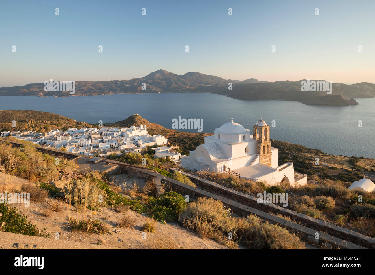 White old town of Plaka with Greek Orthodox church and Milos Bay from Plaka Castle, Plaka, Milos, Cyclades, Aegean - Stock Image