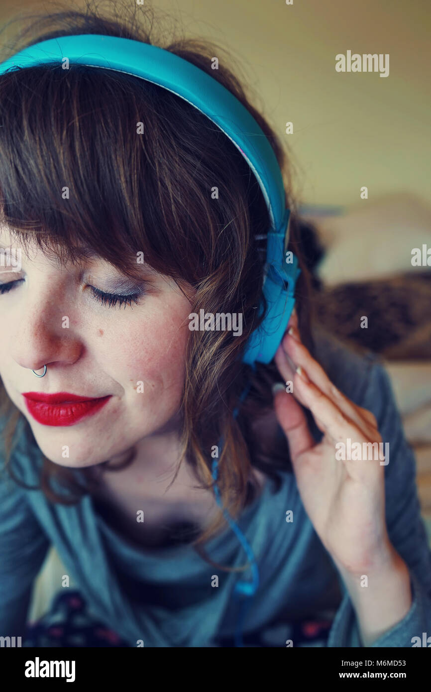 Young woman at home listening to music - Stock Image