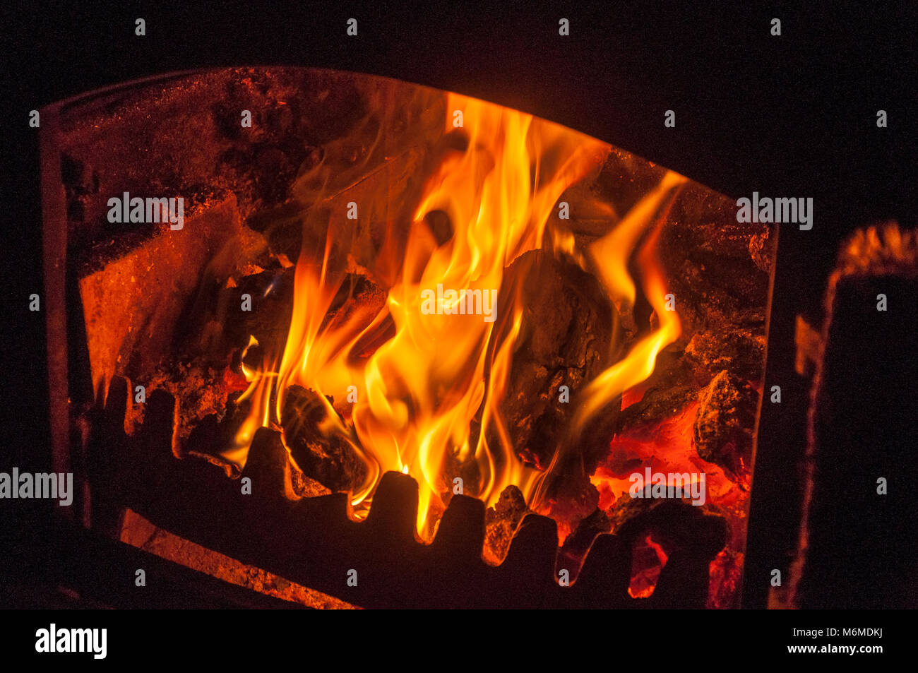 Burning coal and wood in a metal stove - Stock Image