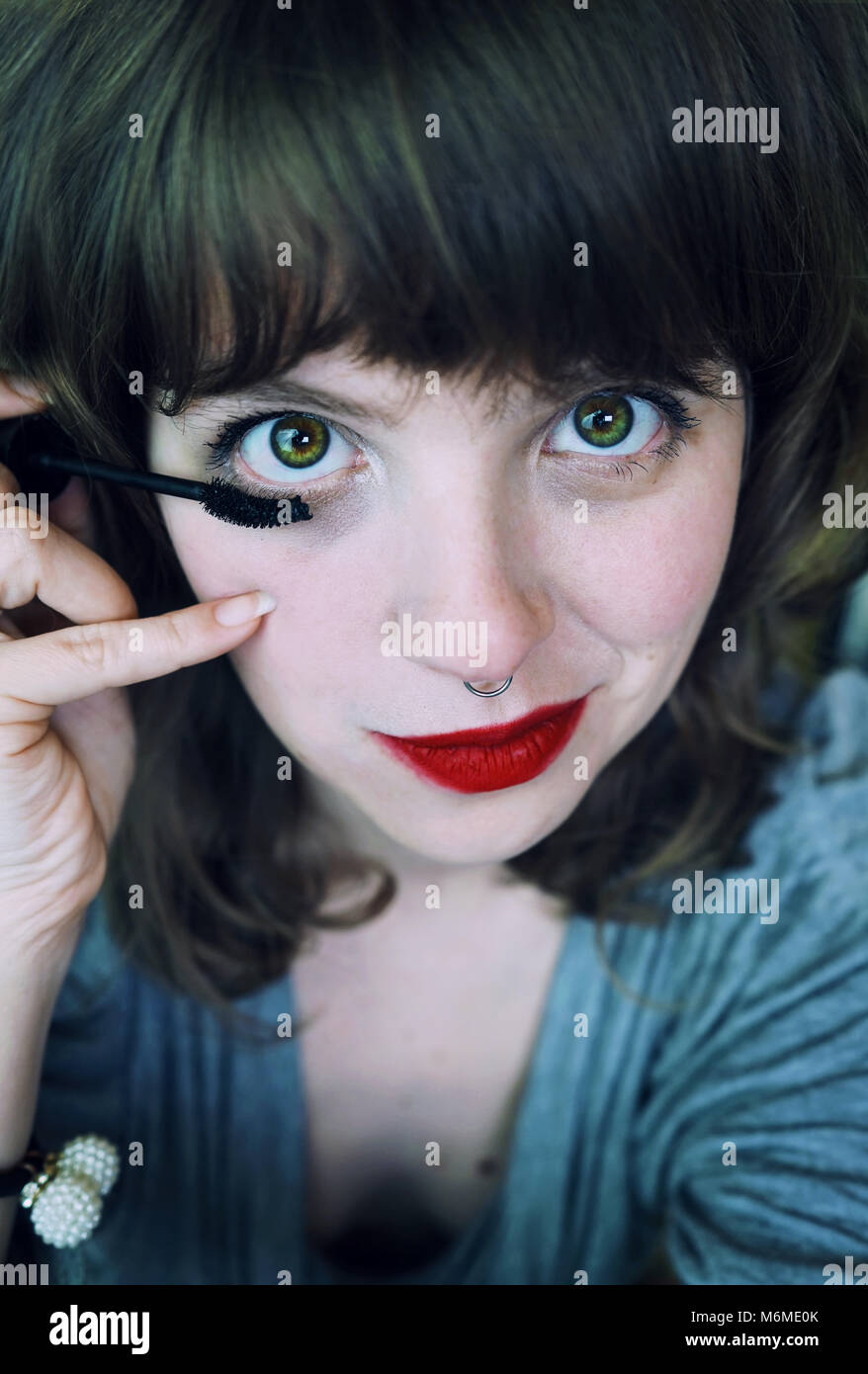 Young woman applying makeup herself - Stock Image