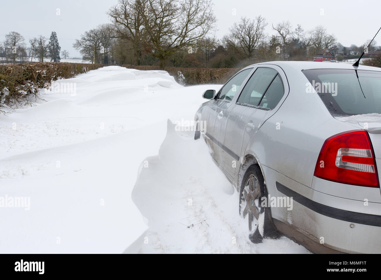 A car stuck in a snow drift in a country lane in Redditch, UK - Stock Image