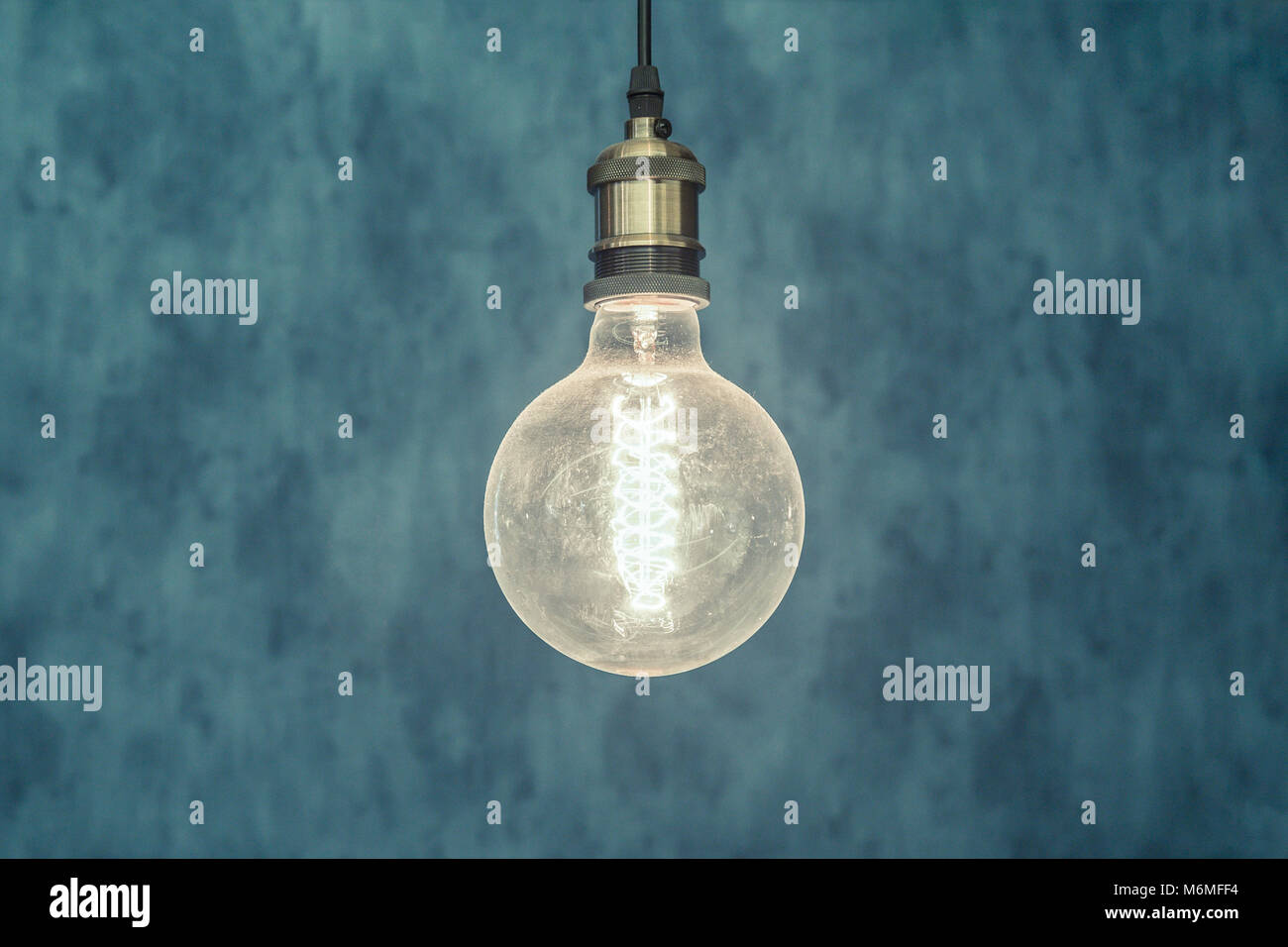 Decorative antique edison style light bulb against blue background. - Stock Image