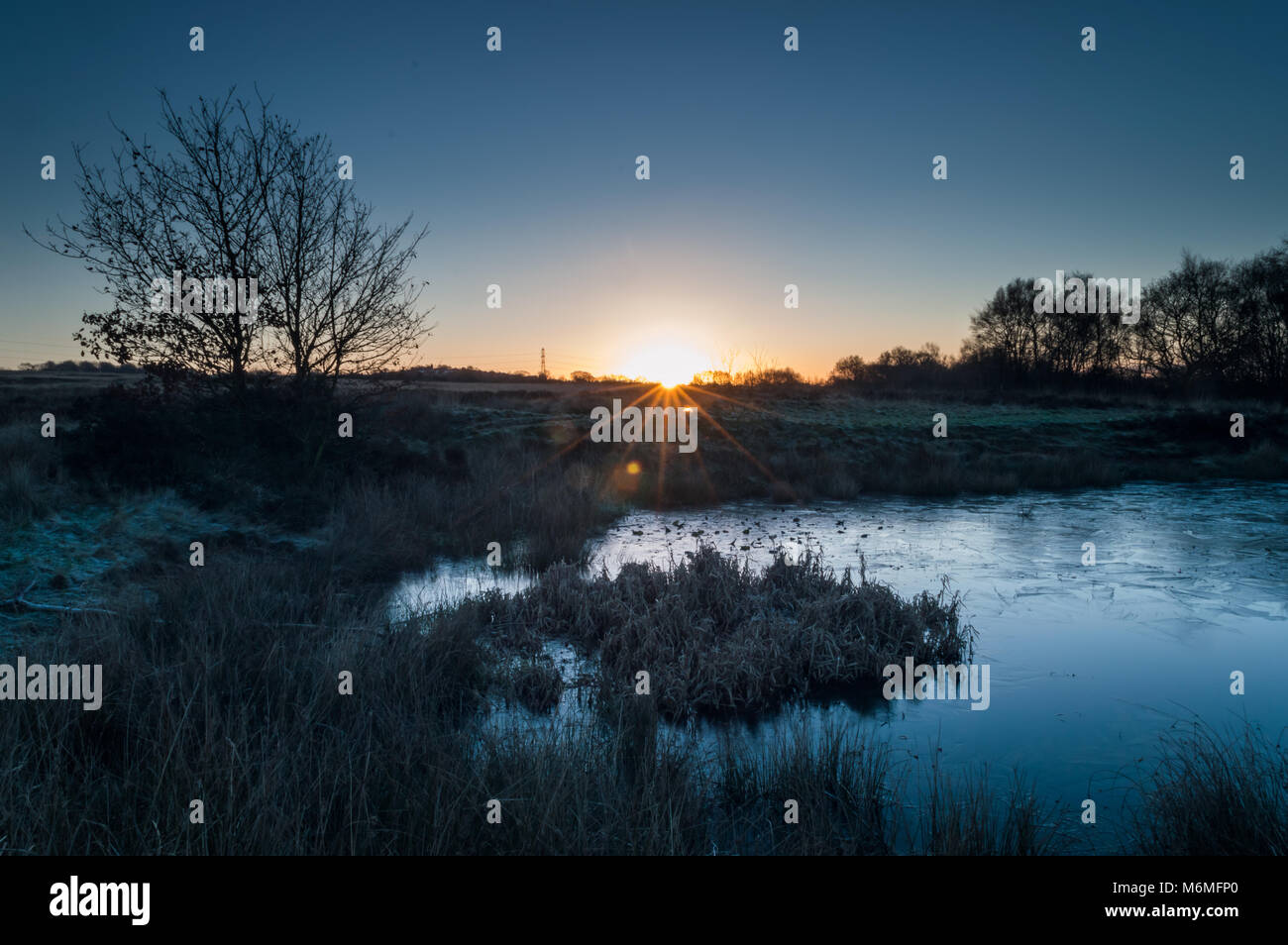 A starburst of dawn light breaking on a frozen pond on Wetley Moor Staffordshire. - Stock Image