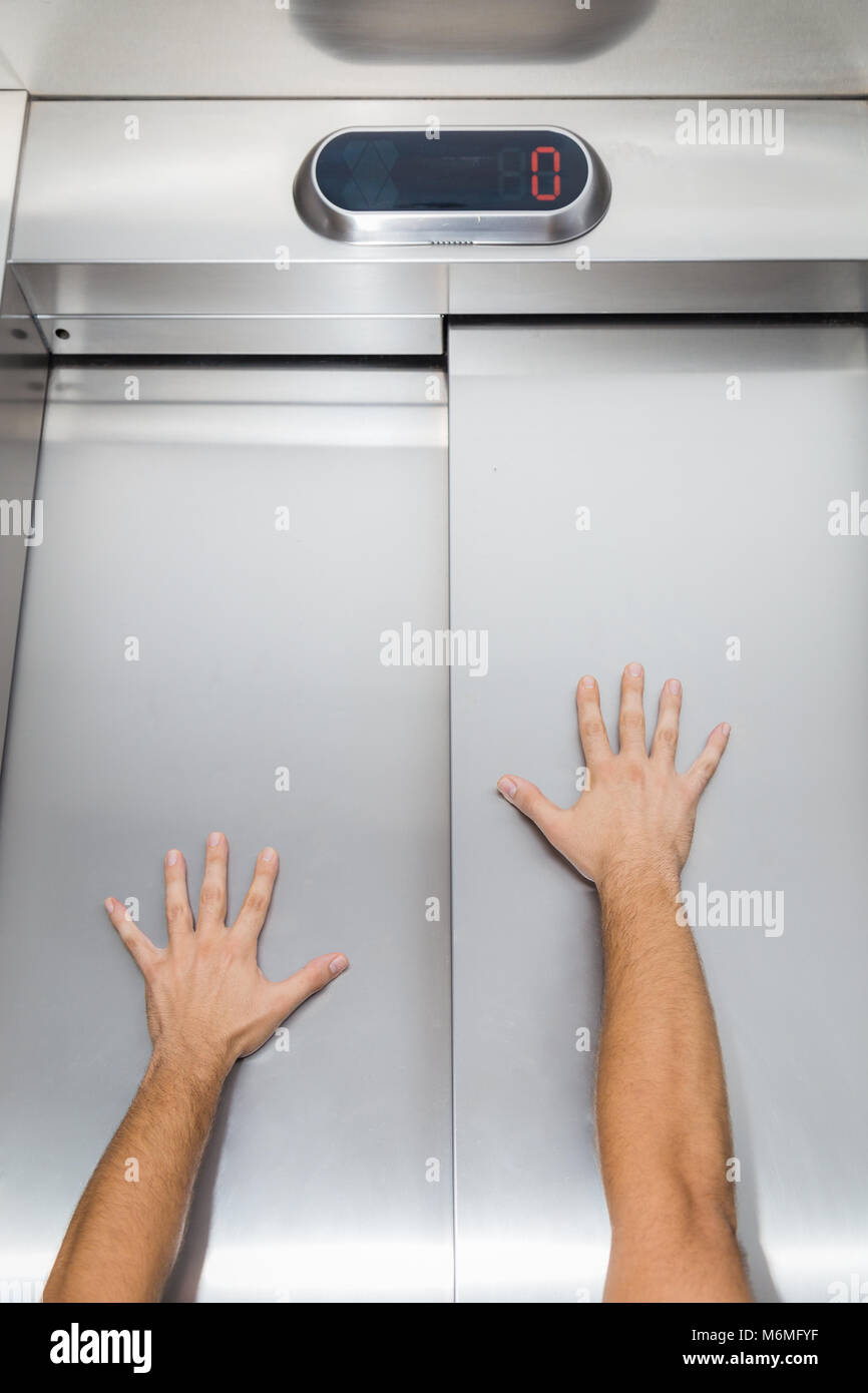 Man hands try to stop and prevent closing elevator door - Stock Image