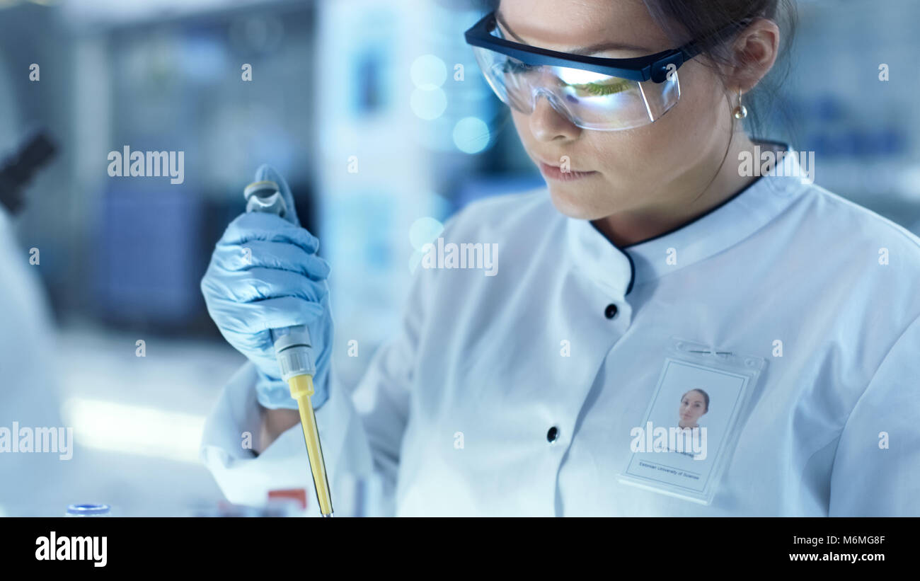 Female Research Scientist Uses Micropipette Filling Test Tubes in a Big Modern Laboratory. In the Background Scientists - Stock Image
