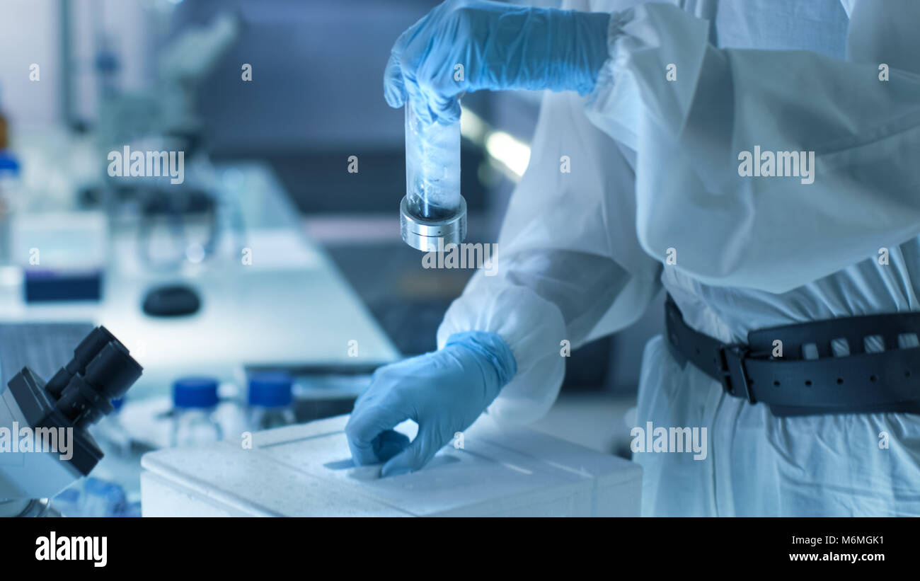 Medical Virology Research Scientist Works in a Hazmat Suit with Mask, She Inspects Test Tube with Isolated Virus - Stock Image