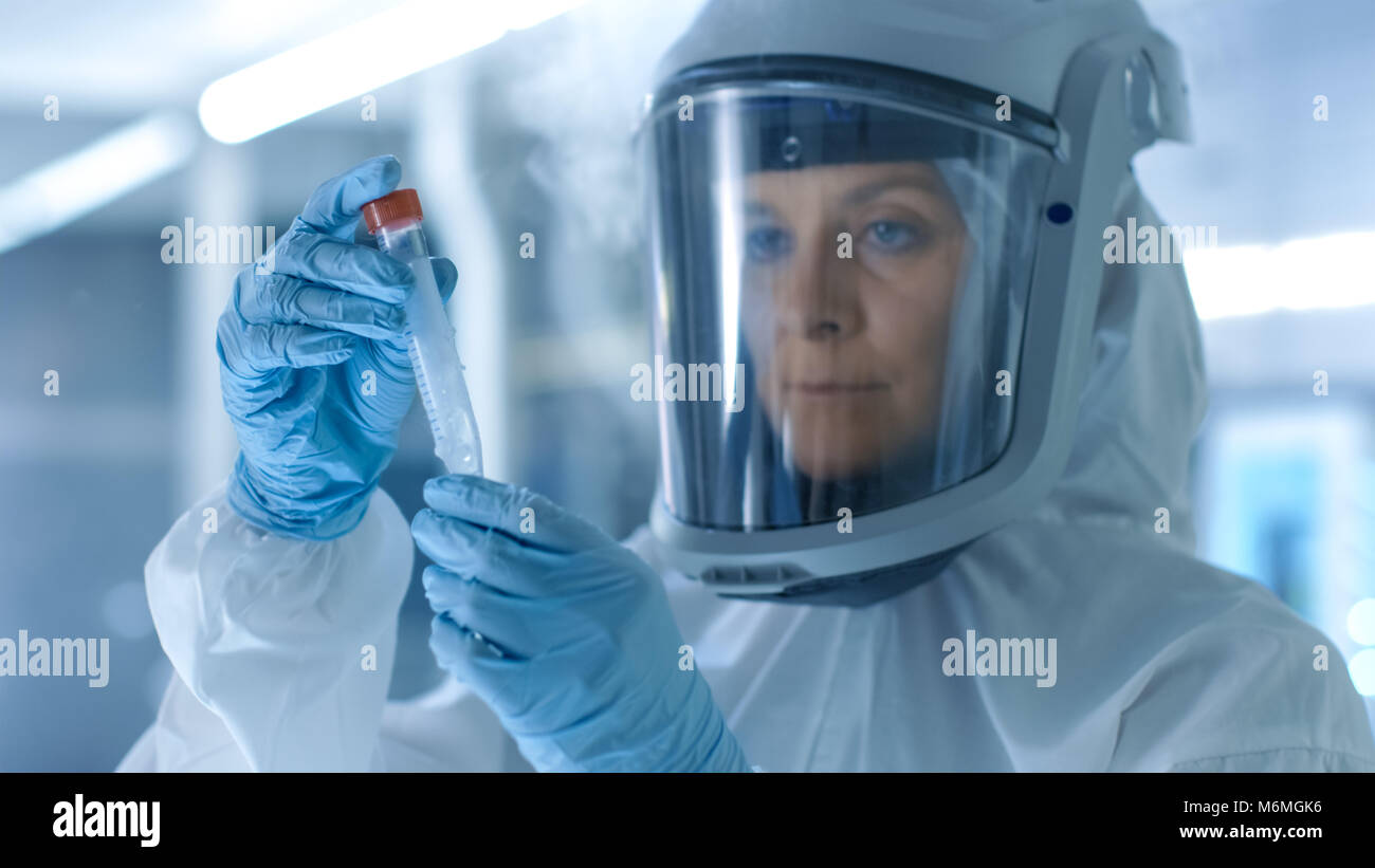 Medical Virology Research Scientist Works in a Hazmat Suit with Mask, Inspects Test Tube with Isolated Virus String - Stock Image