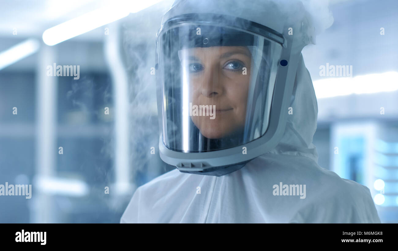 Medical Virology Research Scientist in a Hazmat Suit with Mask, She Inspects Test Tube with Isolated Virus String - Stock Image