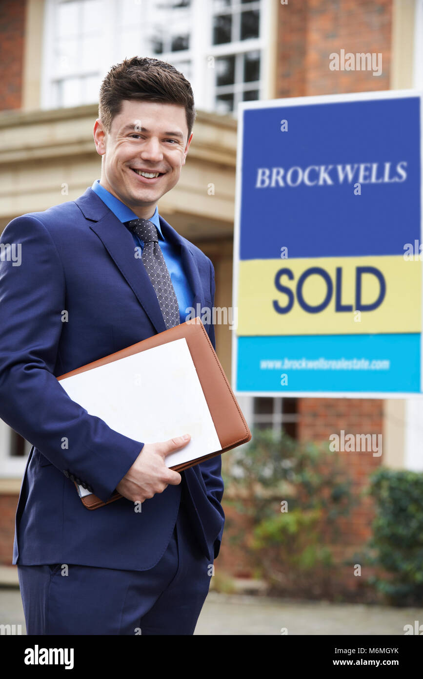 Male Realtor Standing Outside Residential Property With Sold Sign - Stock Image