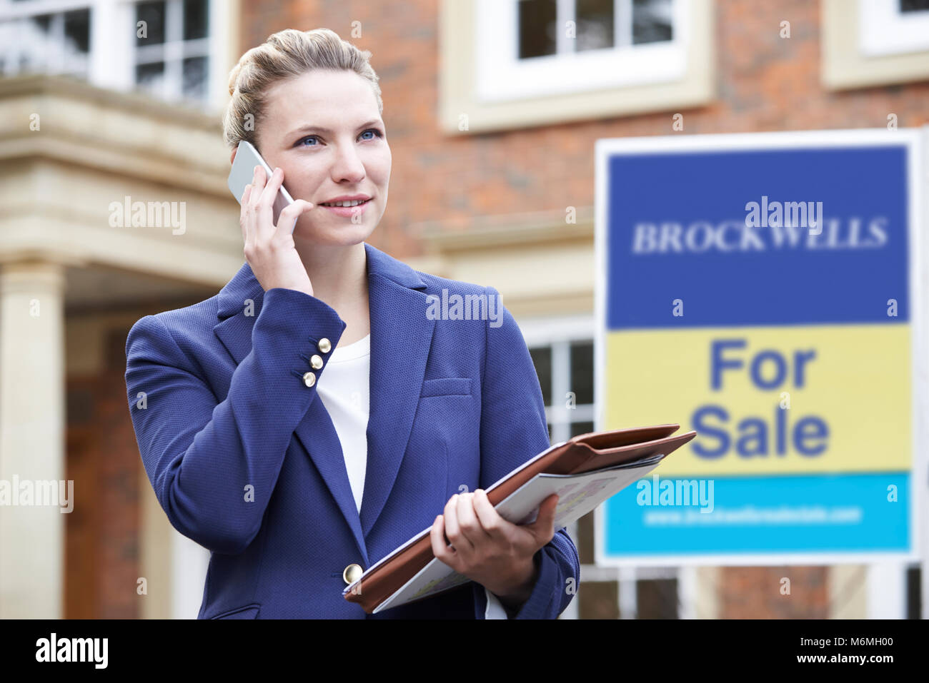 Female Realtor On Phone Outside Residential Property For Sale - Stock Image