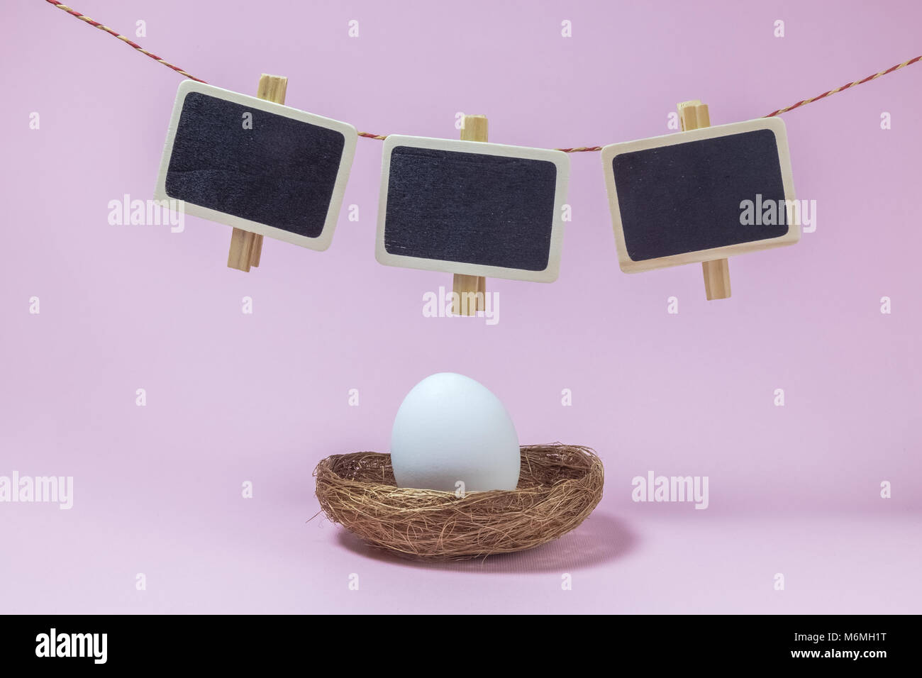 White egg in nest and clothespins with small blackboards hanging above against pastel pink background minimal easter - Stock Image