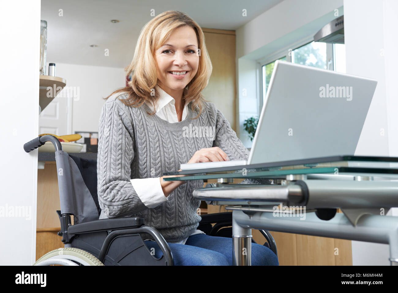 Portrait Of Disabled Woman In Wheelchair Using Laptop At Home - Stock Image
