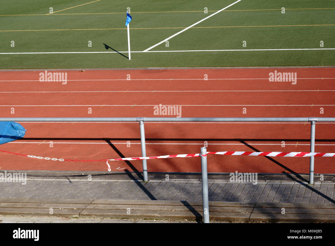 The green lawn surface of a soccer field with the side line and the center line behind a barrier. - Stock Image