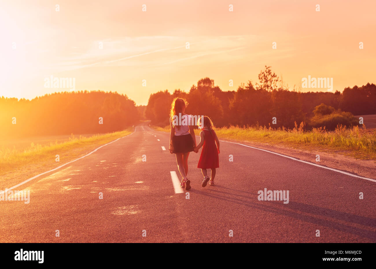 Silhouette two little girls walking on the road . Sisters enjoyed a Holiday over blurred summer nature. Concept - Stock Image