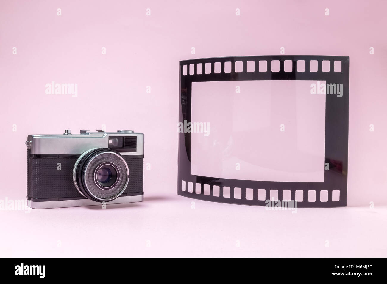 Retro vintage camera and blank frame in photo film shape against ...