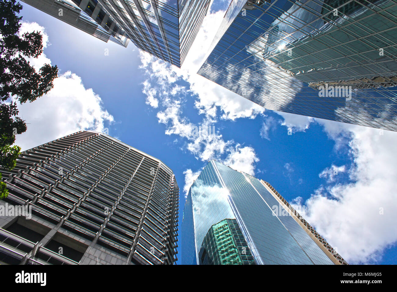 View looking up at blue cloudy sky through skyscrapers reflecting clouds and other buildings in CBD Brisbane Queensland - Stock Image